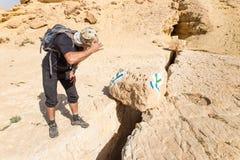 看沙漠足迹标号标志的游人 免版税图库摄影