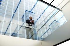 看法一家成功的公司的一位年轻经济学家从下面等待在手机的一个电话 库存照片