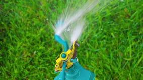 从看法上的庭院喷水隆头慢动作 关闭在绿草,顶视图的洒水喷头喷洒的水 慢 股票录像