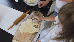 看法上面  有长的头发的小女孩在白色礼服在家做姜饼曲奇饼厨房的面团 婴孩 股票录像
