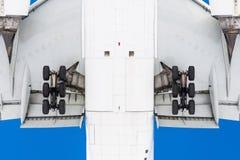 看法从下面在登陆,详细底盘、翼、挡水板、机体和引擎前的飞行飞机下 库存图片
