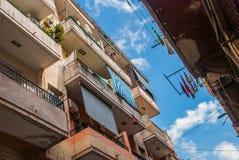 看法从新:通常设有暗门的妓院,垂悬衣物和干燥的绳索的阳台的,与云彩的蓝天 H 免版税库存图片