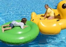 看法和男孩7和在他们的大可膨胀的动物的女孩11浮游物在蓝色水池中间,他们获得很多乐趣 免版税图库摄影