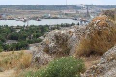 看法在从古城的废墟的前景石头和在工业城市的背景新的地区 库存照片