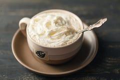 看法在木桌焦点的热奶咖啡咖啡上面在白色泡沫 免版税库存照片