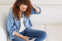 看法在牛仔布衬衣和牛仔裤穿戴的从上面可爱的女性模型,通过手机和耳机听音频轨道,下来 图库摄影