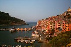 看法在Portovenere和港口有被停泊的小船的,海,五颜六色的大厦,树黎明  库存图片