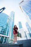 看法摆在城市布局的从下面一个年轻时髦的行家女孩反对高新的摩天大楼和蓝天, 免版税库存照片
