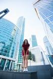 看法获得从下面一名愉快的快乐的妇女乐趣,当摆在反对高摩天大楼在夏日时, 库存图片