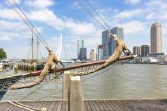 看法通过一艘帆船的船的绳索和船首斜桅在轰烈的大厦的在Erasmus桥梁 免版税库存图片