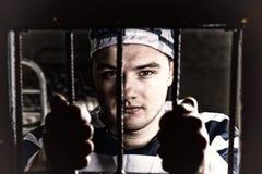 看法通过与监狱酒吧的铁门在年轻囚犯holdin 免版税库存照片