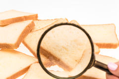 看法通过敬酒在桌上的面包的放大镜 麦子 库存图片