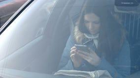 看法通过汽车的挡风玻璃在年轻深色的妇女的看电话的蓝色下来夹克的 股票录像