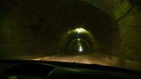 看法通过汽车的挡风玻璃 汽车通过在与昏暗的照明设备和国家的一个岩石做的隧道乘坐 影视素材