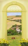 看法通过被成拱形的门、多小山风景和一点村庄 库存图片