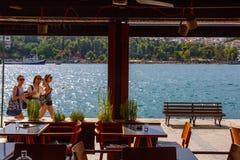 看法通过走沿在卡尔基斯,希腊的散步的三个女孩咖啡馆窗口  免版税库存图片