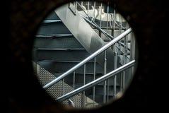 看法通过Bullauge到与2个反对的弯曲的不锈钢台阶和不锈钢栏杆的一个楼梯里 免版税库存图片