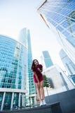 看法从下面有摆在反对现代摩天大楼的完善的图的一名可爱的妇女在商业区, 免版税库存图片