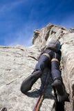 看法从下面登山人,当攀登陡峭的岩石墙壁时 免版税库存照片