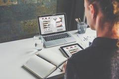 看法从后面,女实业家坐在书桌的和工作 在网上学会的学生 企业规划 免版税图库摄影