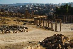 看法破坏卵形论坛和长的有列柱街道或cardo古老希腊罗马城市Gerasa 背景的现代杰拉什 旅游业 库存图片