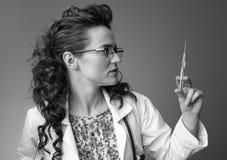 看注射器的儿科医生妇女  图库摄影