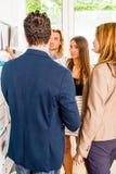 看海报栏的买卖人在办公室 免版税库存照片