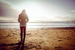 看海的妇女背面图在日落期间 库存图片