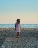 看海的小白肤金发的女孩 免版税库存照片