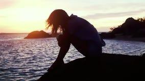 看海的海滩的沉思哀伤的年轻女人在令人惊讶的日落期间 慢的行动 1920x1080 股票视频