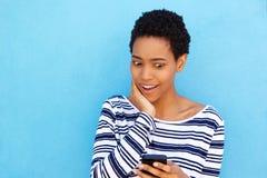 看混淆手机的年轻非洲妇女 库存图片