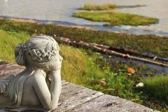 看湖的白人妇女雕象 库存图片