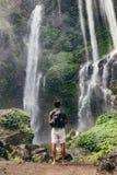 看瀑布的年轻男性远足者 图库摄影