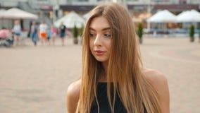 看照相机关闭的浅褐色的头发的年轻女人画象  都市城市街道背景的美女 影视素材