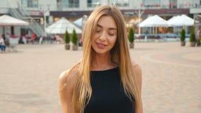 看照相机关闭的面孔浅褐色的头发的年轻女人  都市城市街道背景的画象美女 股票视频