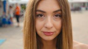 看照相机关闭的面孔浅褐色的头发的年轻女人  都市城市街道背景的画象美女 股票录像