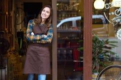 看照相机和倾斜反对一家有机商店的门框的美丽的年轻女推销员 免版税图库摄影