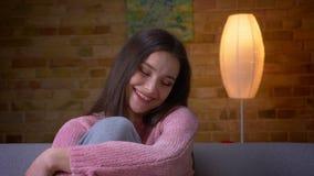 看照相机和微笑充满喜悦的年轻逗人喜爱的深色的白种人女性特写镜头射击坐在a的长沙发 股票视频