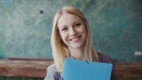 看照相机和微笑在现代办公室的年轻白种人白肤金发的妇女画象  成功的雇员在工作 股票视频