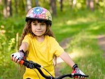 看照相机和微笑的自行车的小女孩 免版税图库摄影