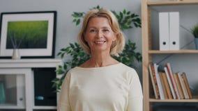 看照相机和微笑的身分的愉快的成熟夫人画象在办公室 影视素材