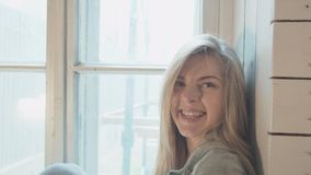 看照相机和微笑的年轻愉快的女孩 微笑的美丽的金发碧眼的女人写sms坐窗口 股票录像