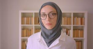 看照相机快乐地微笑在图书馆里的年轻回教女性医生和hijab特写镜头画象玻璃的 股票录像