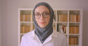 看照相机愉快地微笑在图书馆里的年轻回教女性医生和hijab特写镜头画象玻璃的户内 影视素材