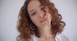 看照相机有背景的年轻俏丽的长发卷曲白种人女性特写镜头射击隔绝在白色 股票录像