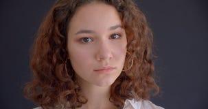 看照相机有背景的年轻俏丽的长发卷曲白种人女性特写镜头画象隔绝在灰色 股票录像