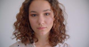 看照相机有背景的年轻俏丽的长发卷曲白种人女性特写镜头画象隔绝在白色 股票视频
