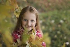 看照相机的一个愉快的微笑的小女孩的画象在秋天公园 逗人喜爱的四岁儿童享用 免版税库存照片
