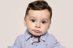 看照相机的一个逗人喜爱的男婴的画象乏味 免版税库存图片