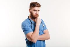 看照相机的一位严肃的沉思男性医生的画象 免版税库存图片